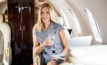 Portrait of beautiful businesswoman having wine in corporate jet